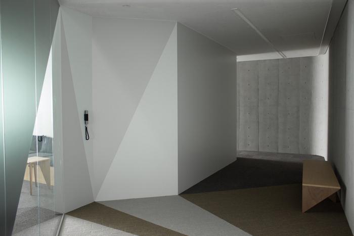 koridor-minimalis-dengan-dinding-beton-abu-abu-dan-lantai-karpet-di-pola